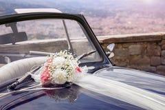Tappningbröllopbil med buketten av blommor på hättan royaltyfria bilder