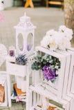 Tappningbröllopsammansättning Vit spjällåda som dekoreras med färgglade blommor, stearinljusställningen och böcker Royaltyfri Fotografi