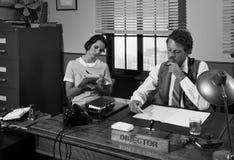 Tappningdirektör och sekreterare som tillsammans arbetar på skrivbordet Arkivfoto