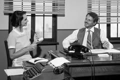 Tappningdirektör och sekreterare som tillsammans arbetar på skrivbordet Royaltyfri Bild
