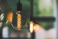 Tappningedison ljus kula som inomhus hänger med andra ljusa kulor Fotografering för Bildbyråer