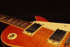 Tappningelkraften slösar gitarrcloseupen på svart bakgrund grunt djupfält royaltyfri fotografi