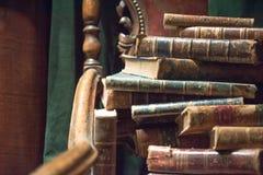 Tappningfåtölj med gamla böcker arkivfoto