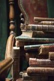 Tappningfåtölj med gamla böcker arkivfoton