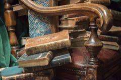 Tappningfåtölj med gamla böcker arkivbilder