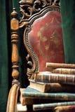 Tappningfåtölj med gamla böcker royaltyfria foton