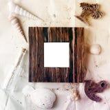 Tappningförlöjligar träfotoramen på hantverkpapper med sand- och havsskal upp royaltyfria foton
