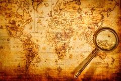 Tappningförstoringsglaset ligger på en forntida världskarta royaltyfria foton