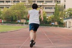 Tappningfilterbild av den tillbaka sikten av den unga asiatiska sprintern som lämnar att starta på löparbana på friidrottstadion royaltyfria foton