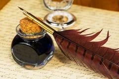 Tappningfjäderpenna och färgpulver Arkivbild