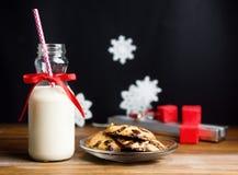 Tappningflaskan av mjölkar med det röda bandet och santas kakor på trätabellen över svart bakgrund royaltyfri bild