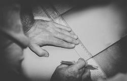 Tappningfoto av arbetaren som använder linjalen för att dra en linje markering på ett wood bräde Fotografering för Bildbyråer
