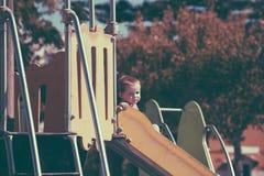 Tappningfoto av barnpojken på glidbana på lekplatsen Royaltyfri Bild