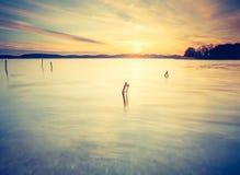 Tappningfoto av den härliga solnedgången över den lugna sjön Royaltyfria Bilder