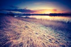 Tappningfoto av den härliga solnedgången över den lugna sjön Royaltyfri Fotografi