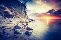 Tappningfoto av den härliga steniga havskusten på soluppgång Arkivfoto