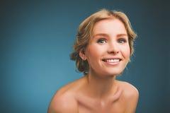 Tappningfoto av en ung kvinna med blont hår och ett toothy leende royaltyfri bild