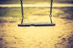 Tappningfoto av tom gunga på barnlekplats royaltyfri bild