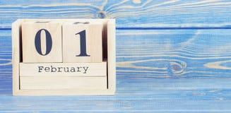 Tappningfoto, Februari 1st datum av 1 Februari på träkubkalender Royaltyfri Foto