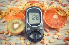 Tappningfoto, Glucometer med resultat, cm, frukter och läkarundersökningpreventivpillerar, sockersjuka, bantning, sund livsstil o Royaltyfri Bild