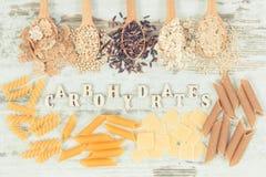 Tappningfoto, inskriftkolhydrater och mat som innehåller mineraler och diet-fiber, sund näring arkivbilder