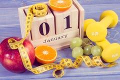 Tappningfoto, kubkalender, frukter, hantlar och måttband, nya år upplösningar arkivbild
