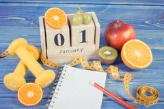 Tappningfoto, kubkalender, frukter, hantlar och måttband, nya år upplösningar Arkivfoto