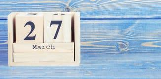 Tappningfoto, mars 27th Datum av 27 mars på träkubkalender Arkivfoto