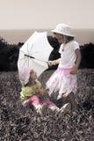 Tappningfoto med flickor med paraplyet på lawn royaltyfri bild