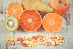 Tappningfoto, nya frukter och färgrika medicinska preventivpillerar, val mellan sund näring och läkarundersökningtillägg Royaltyfri Fotografi
