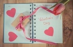 Tappningfoto, skriftlig valentindag i anteckningsbok, ny tulpan, slågen in gåva och hjärtor, garnering för valentin Arkivbild