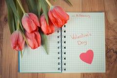 Tappningfoto, skriftlig valentindag i anteckningsbok, nya tulpan och hjärta, garnering för valentin Royaltyfria Foton