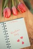 Tappningfoto, skriftlig valentindag i anteckningsbok, nya tulpan och hjärtor, garnering för valentin Arkivfoto