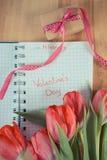 Tappningfoto, skriftlig valentindag i anteckningsbok, nya tulpan och slågen in gåva för valentin Arkivfoto