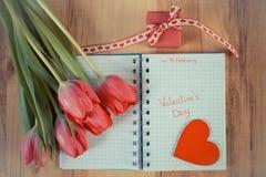 Tappningfoto, skriftlig valentindag i anteckningsbok, nya tulpan, slågen in gåva och hjärta, garnering för valentin Arkivfoto