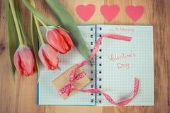 Tappningfoto, skriftlig valentindag i anteckningsbok, nya tulpan, slågen in gåva och hjärtor, garnering för valentin Arkivfoton
