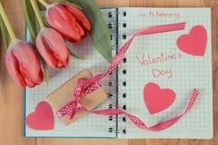 Tappningfoto, skriftlig valentindag i anteckningsbok, nya tulpan, slågen in gåva och hjärtor, garnering för valentin Arkivfoto