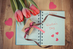 Tappningfoto, skriftlig valentindag i anteckningsbok, nya tulpan, slågen in gåva och hjärtor, garnering för valentin Fotografering för Bildbyråer