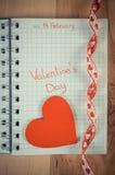 Tappningfoto, skriftlig valentindag i anteckningsbok och röd hjärta med bandet, garnering för valentin Royaltyfria Bilder