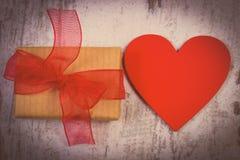 Tappningfoto, slågen in gåva för valentindag och röd hjärta på den gamla trätabellen Arkivbilder