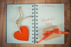 Tappningfotoet, den skriftliga valentindagen i anteckningsbok, slogg in gåvan och hjärta, garnering för valentin Arkivfoton