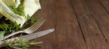 Tappninggaffel och kniv med örter och servetten Royaltyfria Bilder