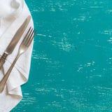 Tappninggaffel och kniv på servett på turkosträ Royaltyfria Bilder