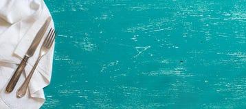 Tappninggaffel och kniv på servett på turkosträ Arkivfoto