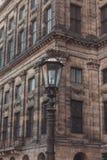 Tappninggatalampa mot Royal Palace på Dam Square i Amsterdam fotografering för bildbyråer