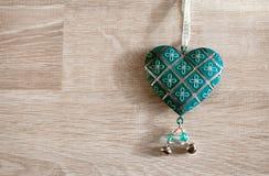 Tappninggrungehjärta som hänger över wood bakgrund Arkivfoton