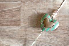 Tappninggrungehjärta som hänger över wood bakgrund Fotografering för Bildbyråer