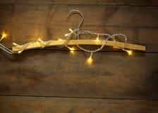 Tappninghängaren med guld- jul värme guld- girlandljus på trälantlig bakgrund Filtrerad bild Royaltyfri Fotografi