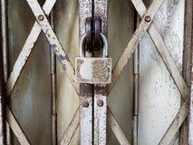 Tappninghänglås på rostiga galler arkivbilder