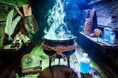 Tappninghäxakruka med den magiska blandningen, blåa drycker och böcker för allhelgonaafton Arkivfoton